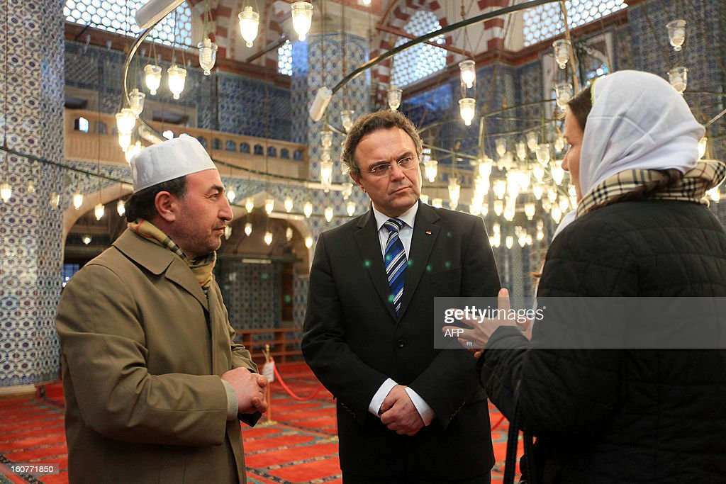 German Interior Minister Hans-Peter Friedrich (C) and Turkish Imam Ismail Karakelle (L) speak with an unidentified woman (R) during a visit to the Rustem Pasha Mosque in Istanbul on February 5, 2013. Friedrich said Turkish authorities knew the US embassy bomber was back home illegally, a day after Turkish premier accused Germany of not keeping him under surveillance during his stay there.