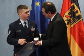 German Interior Minister HansPeter Friedrich awards US Air Force Staff Sergeant Trevor Donald Brewer the German Federal Cross of Merit at a ceremony...