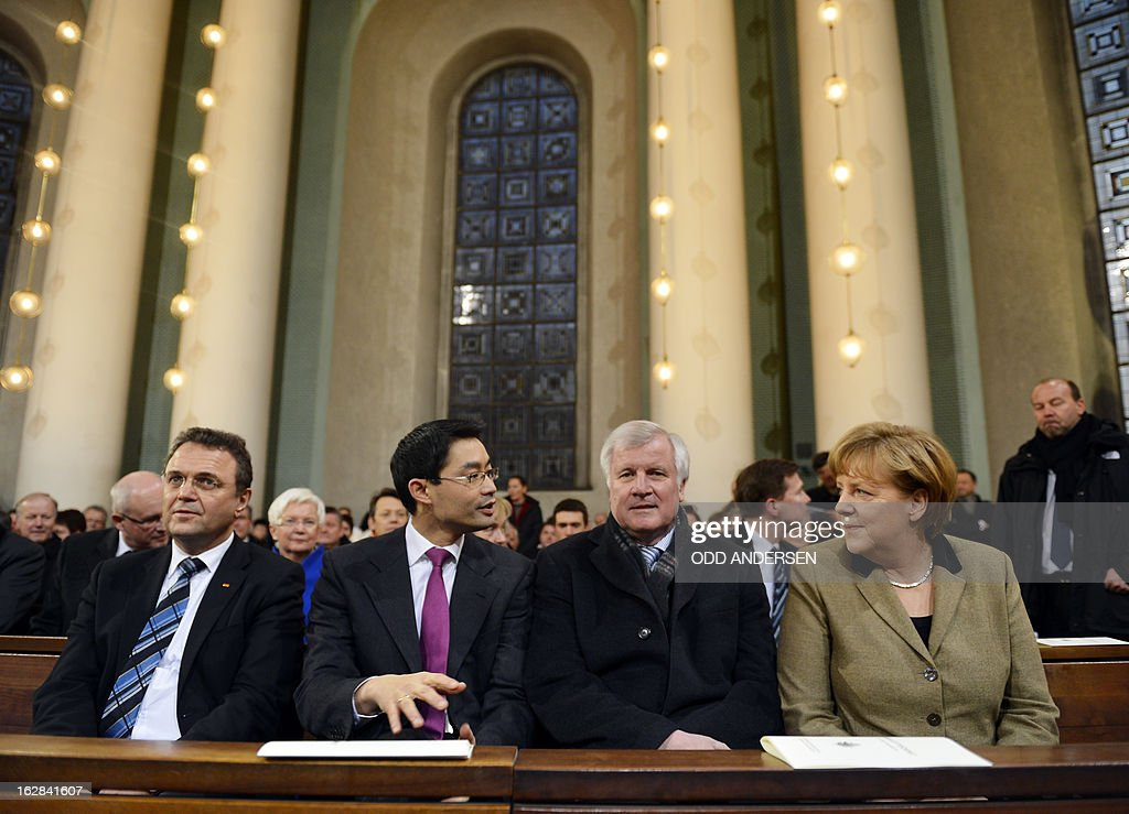German Interior Minister Hans-Peter Friedrich, German Economy Minister and vice-chancellor Philipp Roesler and Bavaria's State Premier Horst Seehofer and German Chancellor Angela Merkel attend a mass service to mark the resignation of Pope Benedict XVI at the St. Hedwig's Cathedral in Berlin on February 28, 2013. The mass coincides with the final hour of Benedict XVI papacy as his powers formally expire at 19:00 GMT.