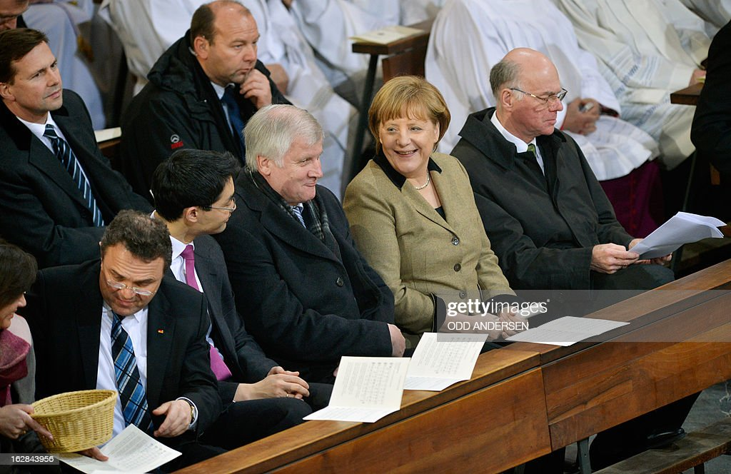 German Interior Minister Hans-Peter Friedrich, German Economy Minister and vice-chancellor Philipp Roesler and Bavaria's State Premier Horst Seehofer, German Chancellor Angela Merkel and German Bundestag President Norbert Lammert attend a mass service to mark the resignation of Pope Benedict XVI at the St. Hedwig's Cathedral in Berlin on February 28, 2013. The mass coincides with the final hour of Benedict XVI papacy as his powers formally expire at 19:00 GMT.