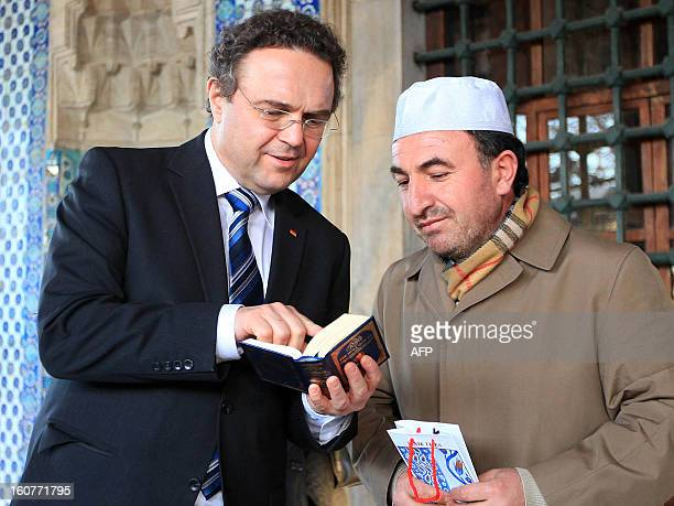 German Interior Minister HansPeter Friedrich holds a copy of the Koran Islam's holy book as he speaks with Turkish Imam Ismail Karakelle during a...