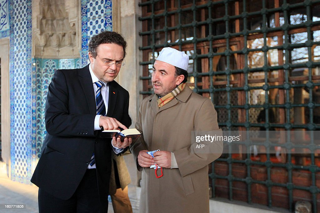 German Interior Minister Hans-Peter Friedrich (L) holds a copy of the Koran, Islam's holy book, as he speaks with Turkish Imam Ismail Karakelle (R) during a visit to the Rustem Pasha Mosque in Istanbul on February 5, 2013. Friedrich said Turkish authorities knew the US embassy bomber was back home illegally, a day after Turkish premier accused Germany of not keeping him under surveillance during his stay there. AFP PHOTO / MIRA