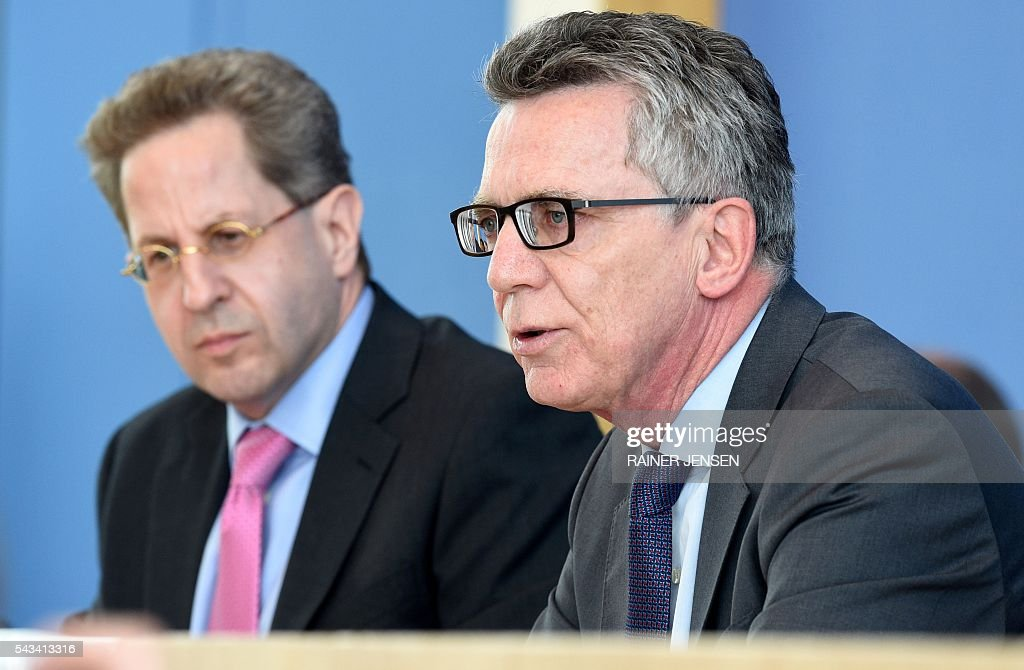 German Interior Minister Thomas de Maiziere (R) and domestic intelligence agency chief Hans-Georg Maassen address a press conference in Berlin on June 28, 2016 as they present the agency's report for the year 2015. / AFP / dpa / Rainer Jensen / Germany OUT