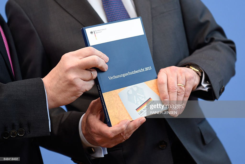 German Interior Minister Thomas de Maiziere (R) and domestic intelligence agency chief Hans-Georg Maassen resent the agency's report for the year 2015 at a press conference in Berlin on June 28, 2016. / AFP / dpa / Rainer Jensen / Germany OUT