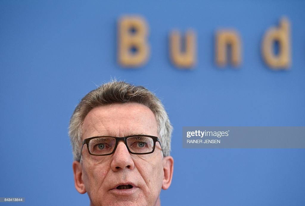 German Interior Minister Thomas de Maiziere and domestic intelligence agency chief address a press conference in Berlin on June 28, 2016 as they present the agency's yearly report for the year 2015. / AFP / dpa / Rainer Jensen / Germany OUT