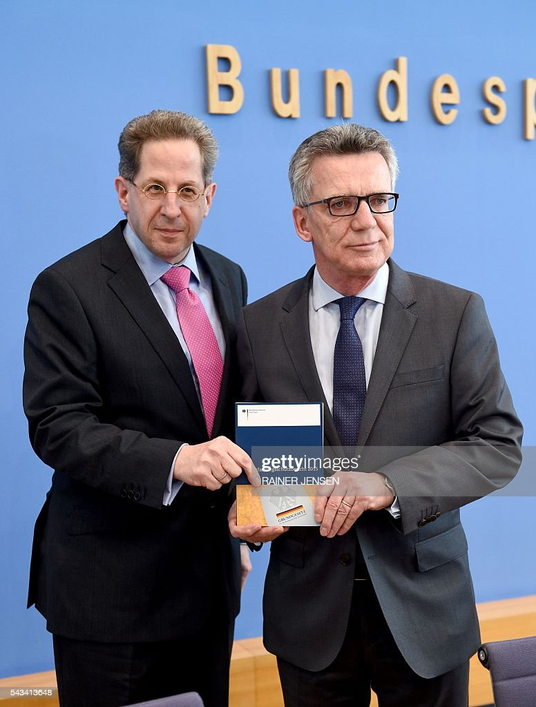 German Interior Minister Thomas de Maiziere (R) and domestic intelligence agency chief Hans-Georg Maassen present the agency's report for the year 2015 at a press conference in Berlin on June 28, 2016. / AFP / dpa / Rainer Jensen / Germany OUT