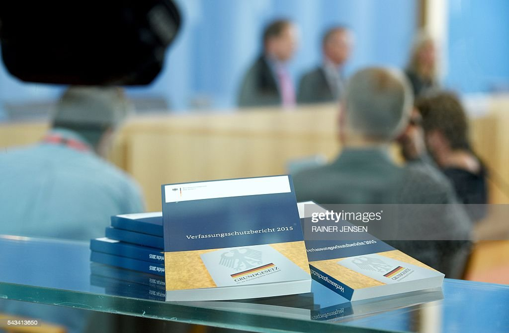 German Interior Minister Thomas de Maiziere (background R) and domestic intelligence agency chief Hans-Georg Maassen address a press conference in Berlin on June 28, 2016 as they present the agency's yearly report for the year 2015. / AFP / dpa / Rainer Jensen / Germany OUT
