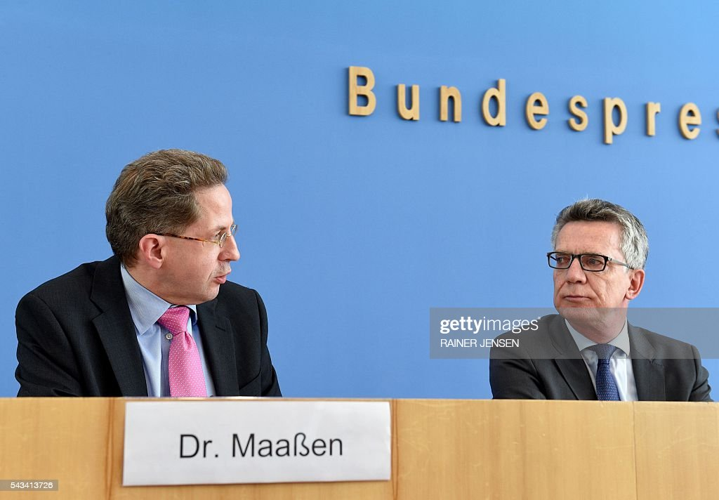German Interior Minister Thomas de Maiziere (R) and domestic intelligence agency chief Hans-Georg Maassen address a press conference in Berlin on June 28, 2016 as they present the agency's yearly report for the year 2015. / AFP / dpa / Rainer Jensen / Germany OUT