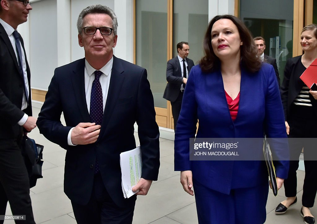 German Interior Minister Thomas de Maiziere shakes hands with German Labour and Social Minister Andrea Nahles arrive for a press conference on the integration issue on May 24, 2016 in Berlin. / AFP / John MACDOUGALL