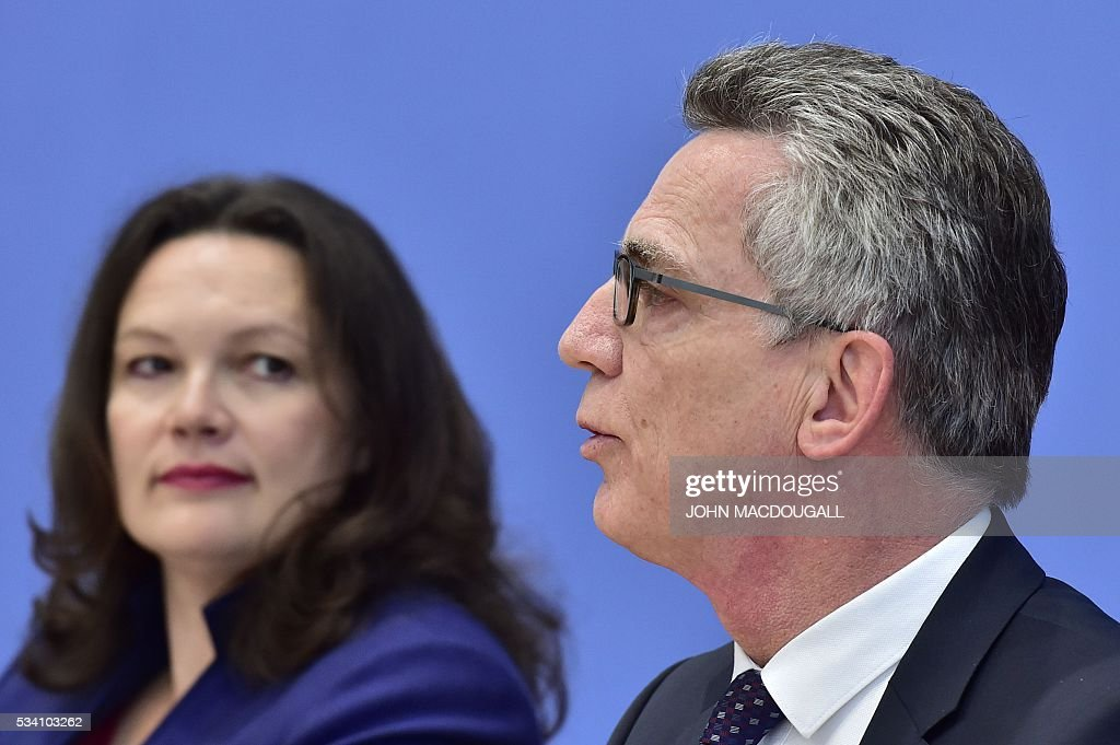 German Interior Minister Thomas de Maiziere and German Labour and Social Minister Andrea Nahles attend a press conference on the integration issue on May 25, 2016 in Berlin. / AFP / John MACDOUGALL