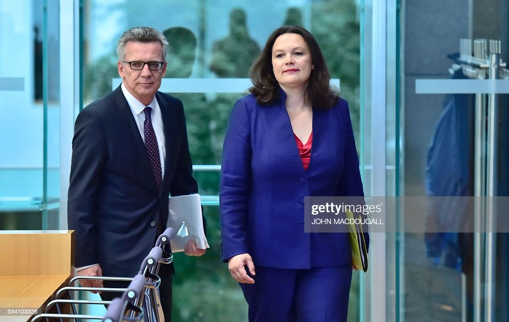 German Interior Minister Thomas de Maiziere (L) and German Labour and Social Minister Andrea Nahles arrive to give a press conference on the integration issue on May 25, 2016 in Berlin. / AFP / John MACDOUGALL
