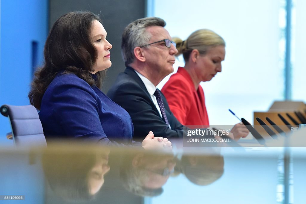 German Interior Minister Thomas de Maiziere (C) and German Labour and Social Minister Andrea Nahles (L) give a press conference on the integration issue on May 25, 2016 in Berlin. / AFP / John MACDOUGALL