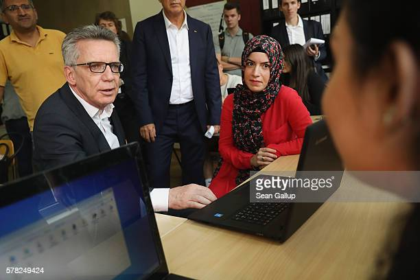 German Interior Minister Thomas de Maiziere chats with trainees in an accounting class at the BWK job training center on July 21 2016 in Berlin...