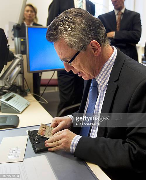 German Interior minister Thomas de Maiziere fits his new biometric ID card in his wallet after collecting it at the Schoeneberg town hall in Berlin...