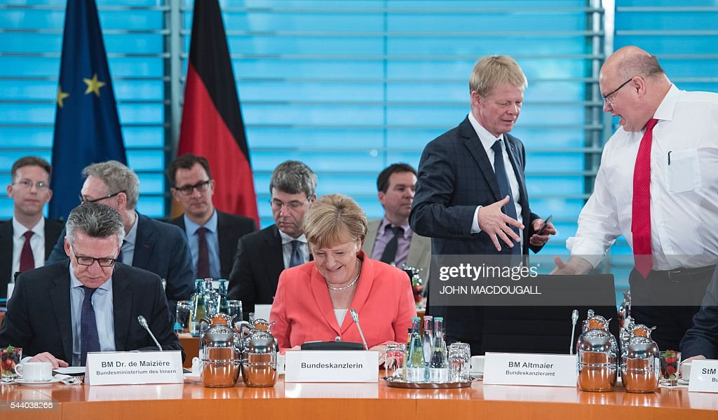 German Interior Minister Thomas de Maiziere, German Chancellor Angela Merkel, DGB (Confederation of German Trade Unions) chief Reiner Hoffmann and German Chief of Staff Peter Altmaier take part in a meeting with associations and organisations involved in helping refugees, at the chancellery in Berlin on July 1, 2016. / AFP / JOHN