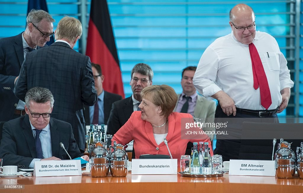 German Interior Minister Thomas de Maiziere, German Chancellor Angela Merkel and German Chief of Staff Peter Altmaier take part in a meeting with associations and organisations involved in helping refugees, at the chancellery in Berlin on July 1, 2016. / AFP / JOHN