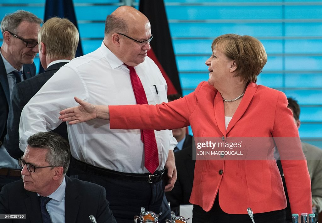 German Interior Minister Thomas de Maiziere, German Chief of Staff Peter Altmaier and German Chancellor Angela Merkel take part in a meeting with associations and organisations involved in helping refugees, at the chancellery in Berlin on July 1, 2016.