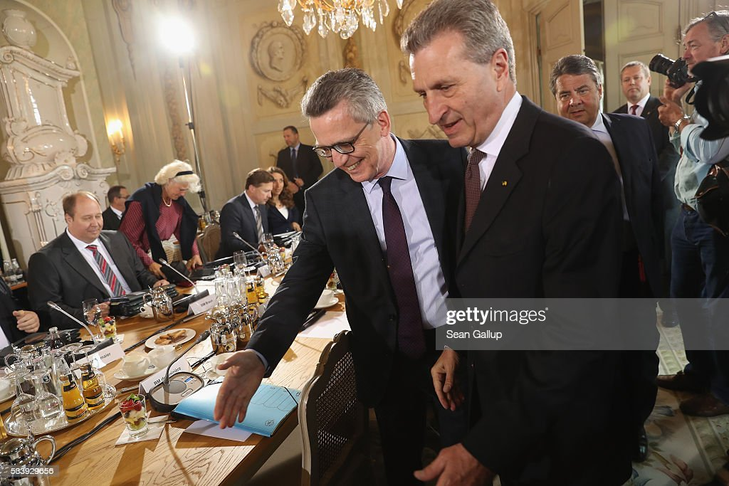 German Interior Minister <a gi-track='captionPersonalityLinkClicked' href=/galleries/search?phrase=Thomas+de+Maiziere&family=editorial&specificpeople=618845 ng-click='$event.stopPropagation()'>Thomas de Maiziere</a> (C) gestures to show European Commissioner for Digital Economy and Society Guenther Oettinger to his chair at a meeting of the German government cabinet at Schloss Meseberg palace on May 24, 2016 in Gransee, Germany. The government cabinet is meeting at Schloss Meseberg for a two-day retreat.