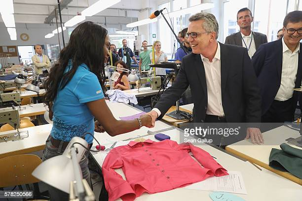 German Interior Minister Thomas de Maiziere greets trainee Tola Usharo from Nigeria in the sewing workshop at the BWK job training center on July 21...