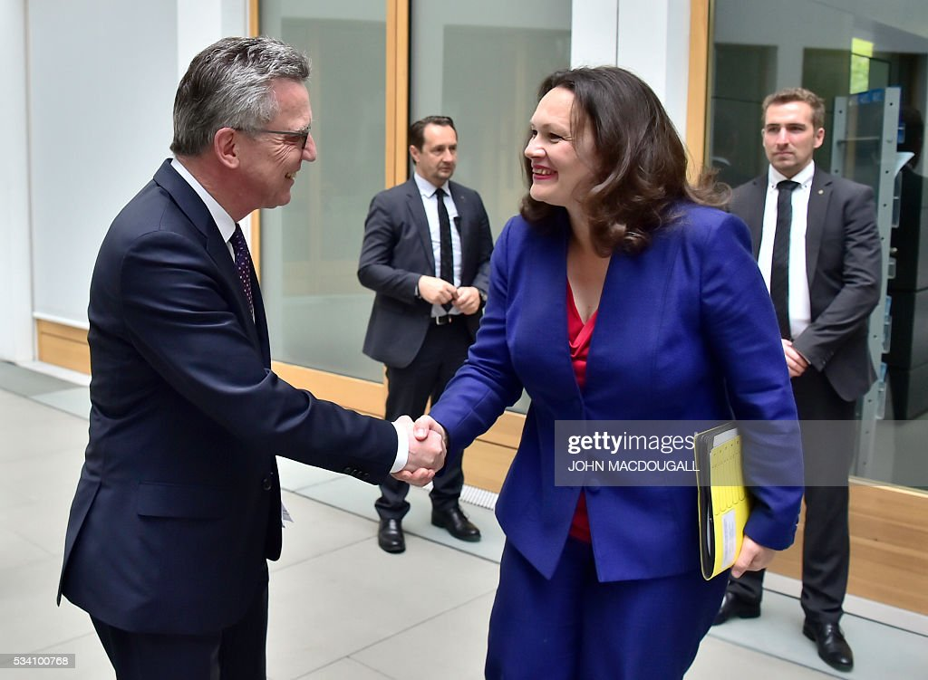 German Interior Minister Thomas de Maiziere shakes hands with German Labour and Social Minister Andrea Nahles prior to a press conference on the integration issue on May 24, 2016 in Berlin. / AFP / John MACDOUGALL