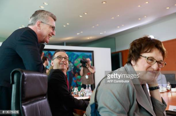 German Interior Minister Thomas de Maiziere shares a smile with German Justice Minister Heiko Maas as German Economy and Energy Minister Brigitte...