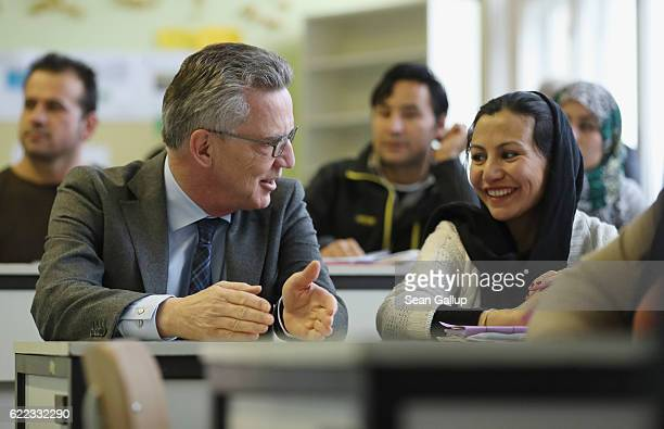German Interior Minister Thomas de Maiziere sits next to Golale Nori a young woman from Afghanistan who arrived in Germany with her husband and two...