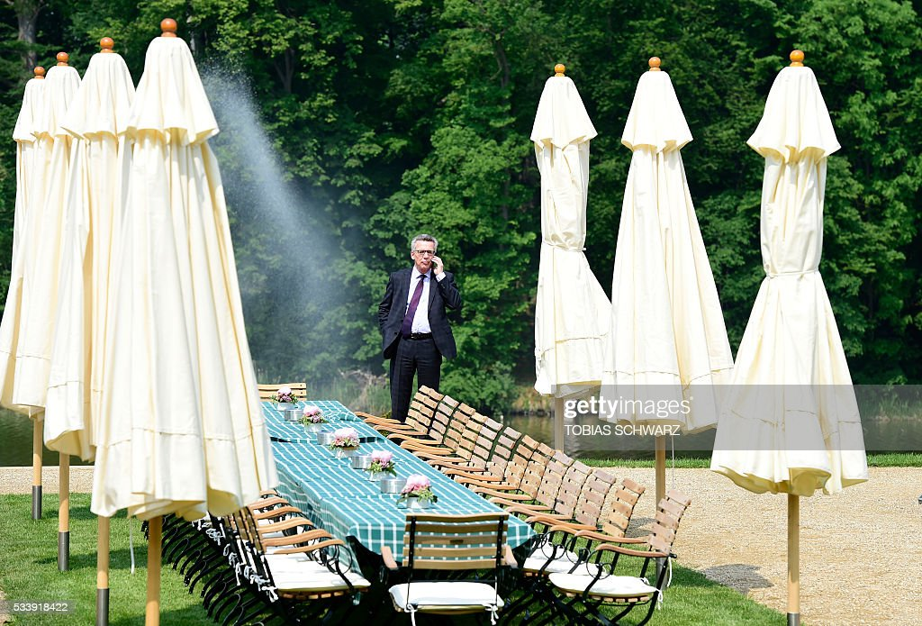 German Interior Minister Thomas de Maiziere speaks on the phone during a closed meeting of the German cabinet at Meseberg Palace on May 24, 2016 in Meseberg, northeastern Germany. / AFP / TOBIAS