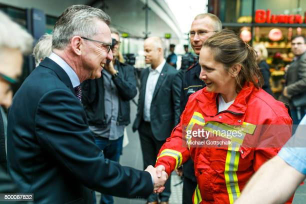 German Interior Minister Thomas de Maiziere talks to a female member of Berlin fire brigade during his visit to the police station of German...