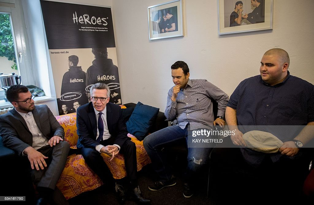 German Interior Minister Thomas de Maiziere (2ndL) talks with participants of the project 'Heroes' aimed at people issued from immigrant background on May 25, 2016 in Berlin. / AFP / POOL / Kay Nietfeld