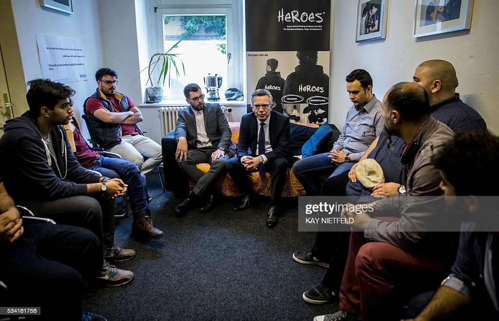 German Interior Minister Thomas de Maiziere (C) talks with participants of the project 'Heroes' aimed at people issued from immigrant background on May 25, 2016 in Berlin. / AFP / POOL / Kay Nietfeld