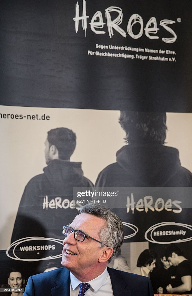 German Interior Minister Thomas de Maiziere visits the headquarters of the project 'Heroes' aimed at people issued from immigrant background on May 25, 2016 in Berlin. / AFP / POOL / Kay Nietfeld