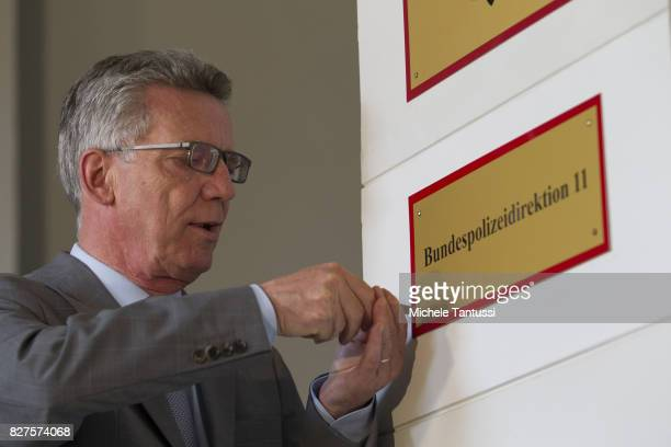 German Interior Minister Thomas de Maziere secures a door sign reading Bundespolizei or Federal Police during the opening of the new Headquarters on...