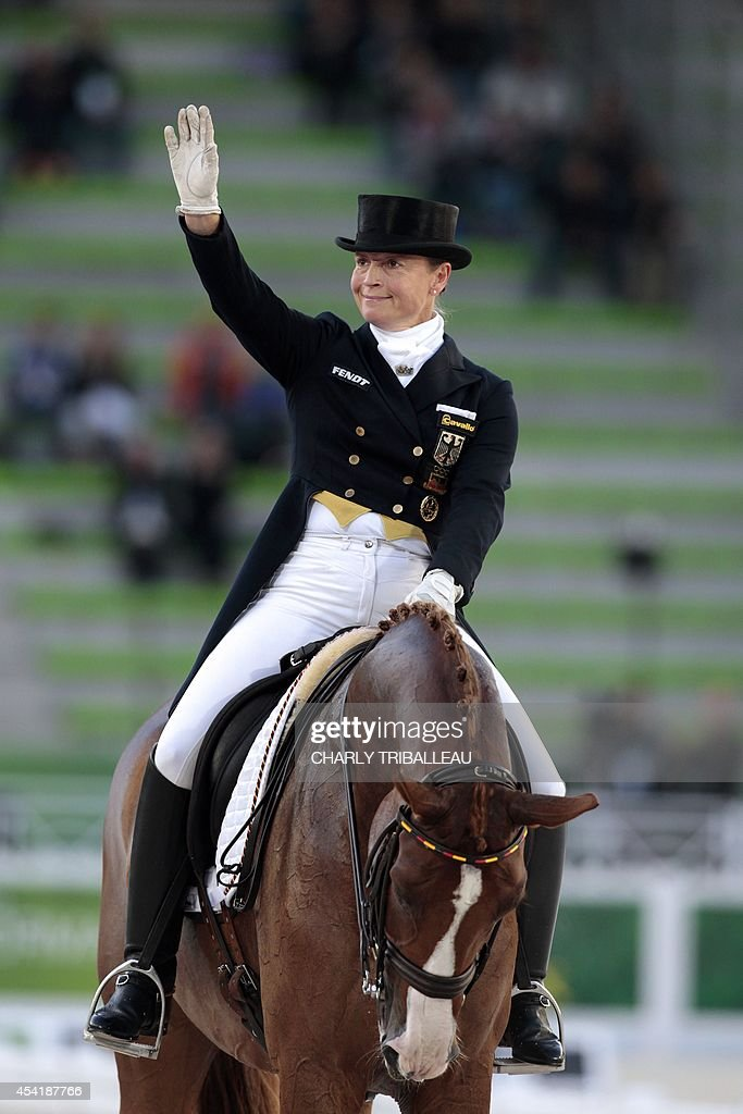 German Isabell Werth waves on Bella Rosa 2 on August 26, 2014 during the second session of the Dressage Grand Prix of the 2014 FEI World Equestrian Games at D'Ornano Stadium in the northwestern French city of Caen. TRIBALLEAU