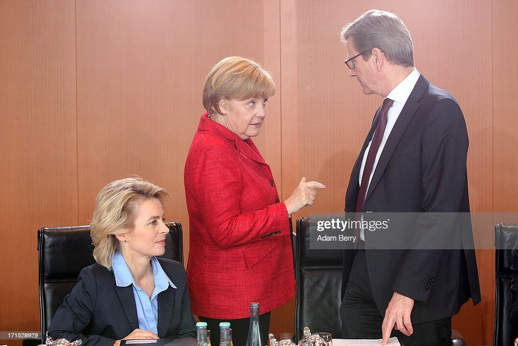 German Labor Minister <a gi-track='captionPersonalityLinkClicked' href=/galleries/search?phrase=Ursula+von+der+Leyen&family=editorial&specificpeople=4249207 ng-click='$event.stopPropagation()'>Ursula von der Leyen</a>, German Chancellor <a gi-track='captionPersonalityLinkClicked' href=/galleries/search?phrase=Angela+Merkel&family=editorial&specificpeople=202161 ng-click='$event.stopPropagation()'>Angela Merkel</a>, and German Foreign Minister <a gi-track='captionPersonalityLinkClicked' href=/galleries/search?phrase=Guido+Westerwelle&family=editorial&specificpeople=208748 ng-click='$event.stopPropagation()'>Guido Westerwelle</a> arrive for the weekly German federal Cabinet meeting on June 26, 2013 in Berlin, Germany. High on the morning's agenda was discussion of the country's 2014 federal budget.
