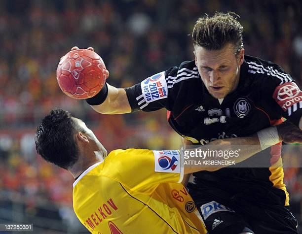 German Lars Kaufmann figths with Macedonian Vladimir Temelkov during the Men's EHF Euro 2012 Handball Championship match Macedonia vs Germany on...