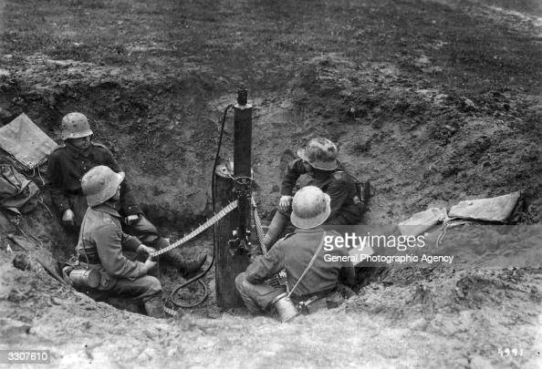 A German machine gun crew with their weapon in a shell crater circa 1916 The gun is swivelmounted on an upright post and watercooled via the tubing...
