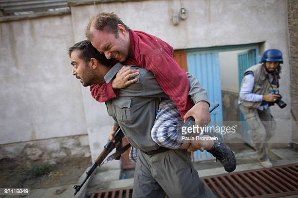 German man with a broken foot is carried away from the scene of a suicide bomb attack on an international guest house October 28 2009 in Kabul...