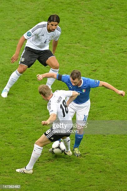 German midfielder Toni Kroos and German midfielder Sami Khedira vie with Italian forward Antonio Cassano during the Euro 2012 football championships...