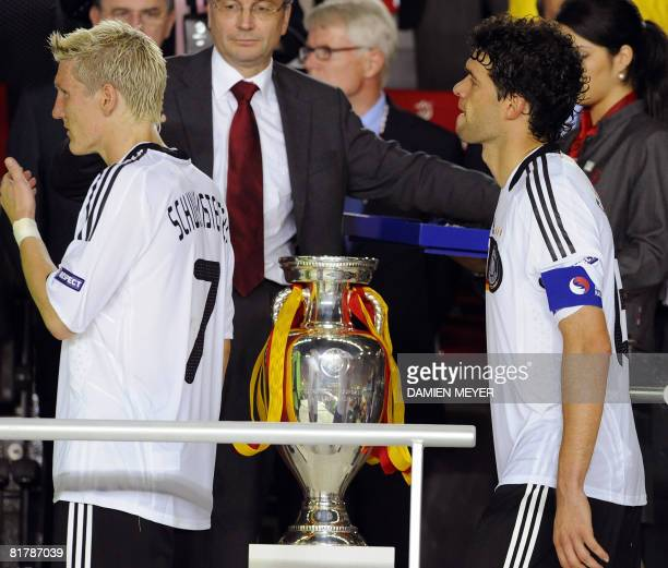 German midfielders Bastian Schweinsteiger and Michael Ballack walk by the trophy after Spain won the Euro 2008 championships final football match...