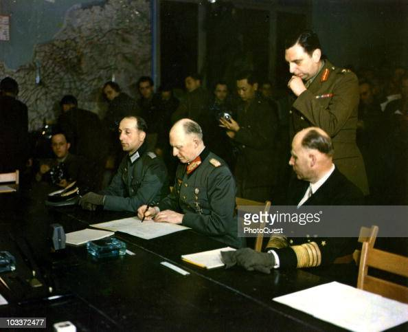 German military commander Generaloberst Alfred Jodl signs the German Instrument of Surrender Reims France May 7 1945 Seated on his right is Major...