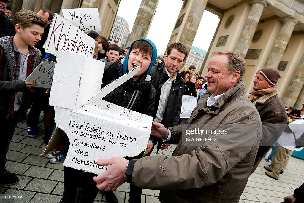 German Minister for Economic Cooperation and Development Dirk Niebel (R) talks with pupils demonstrating with a paper toilet reading 'not to have a toilet is harmful to health' on World Water Day, March 22, 2013 in front of the Brandenburg Gate in Berlin. According to informations provided by Unicef and WHO, more than 780 million people worldwide are not supplied with clean water.