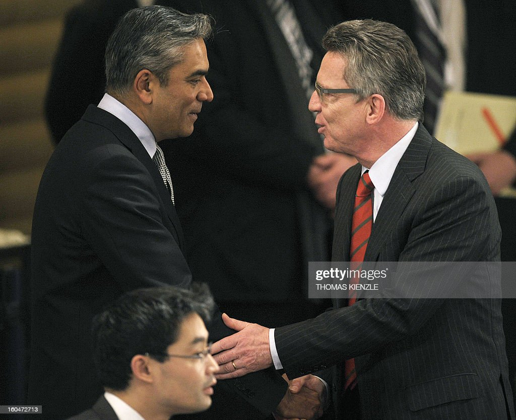 German Minister of Defense Thomas de Maiziere (R) shakes hand with Anshu Jain, co-chairman of the Deutsche Bank AG during the opening session of the Munich Security Conference on February 1, 2013 in Munich, southern Germany as world leaders, ministers and top military gather for talks with the spotlight on Syria, Mali and Iran.