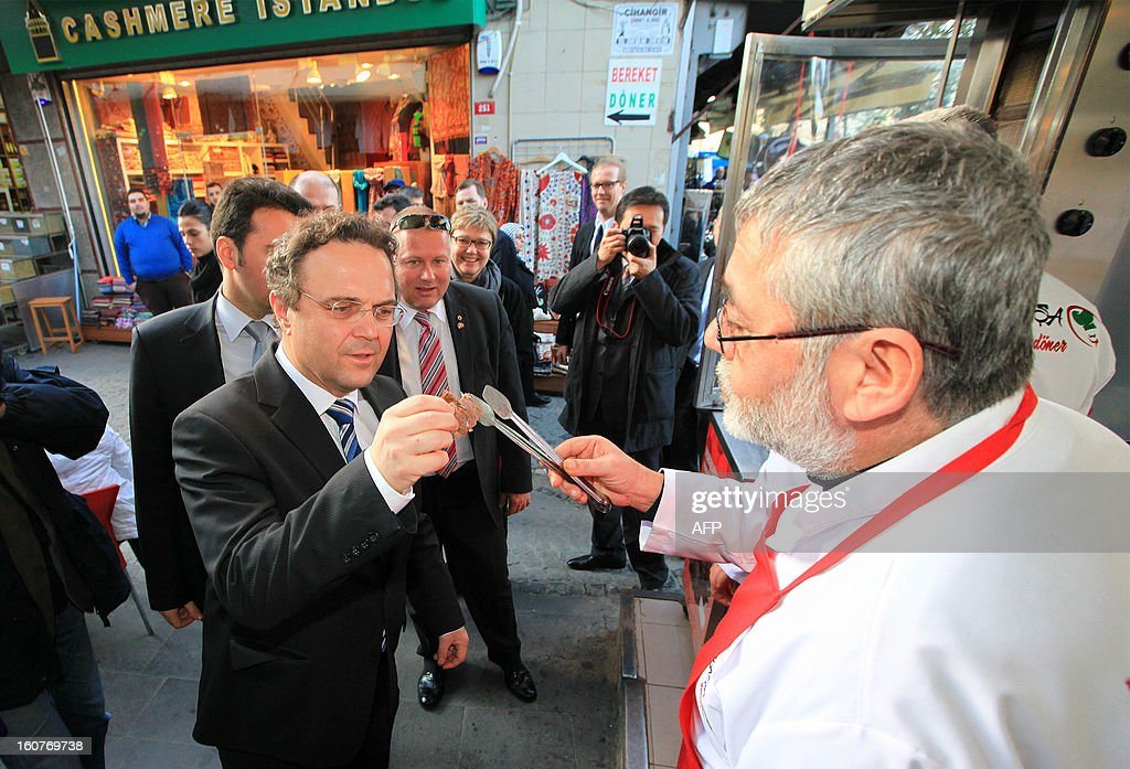 German Minister of the Interior Hans Peter Friedrich (L) is welcomed by a Turkish vendor during his visit to Istanbul, on February 5, 2013. Friedrich is on an official visit in Turkey. AFP PHOTO/MIRA