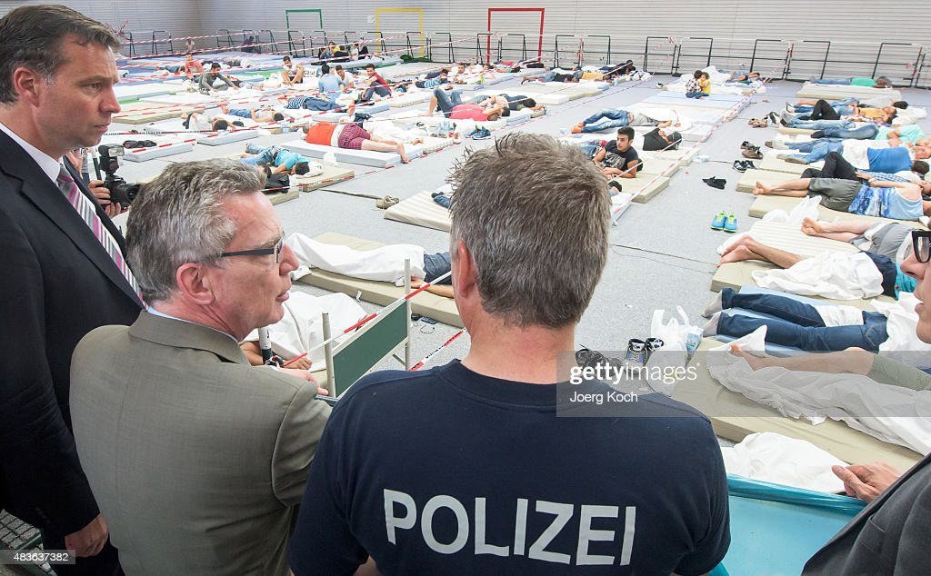 German Minister of the Interior Thomas de Maizere (CDU, C) visits an initial registration center of the German federal police (Bundespolizei) on August 11, 2015 in Deggendorf, Germany. The centre processes refugees who have arrived in Germany by crossing the nearby Austrian border. Bavaria is currently struggling to cope with the daily arrival of hundreds of refugees, mostly from Afghanistan, Syria and Iraq and most of whom arrive via the Balkans through Austria. Germany is expecting over 400,000 refugees and migrants to arrive this year and apply for asylum in a phenomenon that is straining both the budgets and the social cohesion of local communities.
