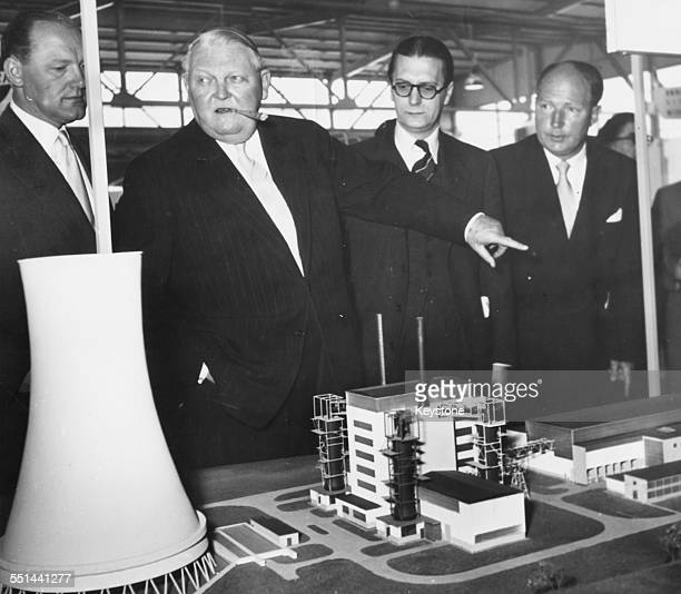 German Minister of Trade Dr Ludwig Erhard with businessmen H A Underwood and Herr Bezold viewing a model of Calder Hall atomic power station at the...