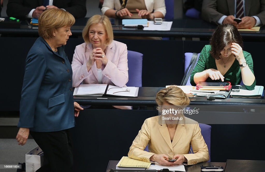 German Minister of Work and Social Issues Ursula von der Leyen (in yellow) operates a smartphone as German Chancellor Angela Merkel (L) walks by and other female members of the German government sit nearby prior to debates over quotas for women in management positions at German corporations on April 18, 2013 in Berlin, Germany. Von der Leyen, a Christian Democrat (CDU), has pushed for quotas, though is at odds on the subject with much of her party, including Chancellor Merkel.