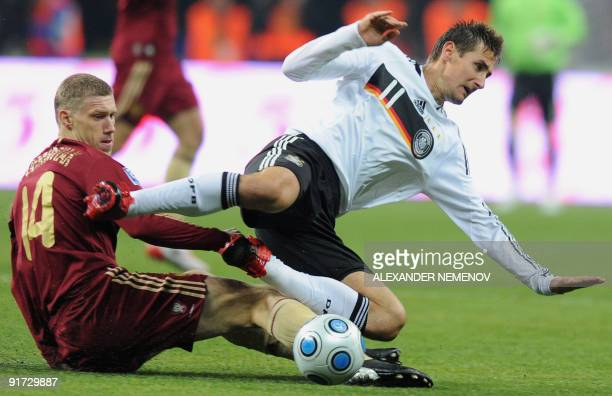 German Miroslav Klose fights for the ball with Russian Pavel Pogrebnyak in Moscow on October 10 during a European Group Four match qualifier for the...