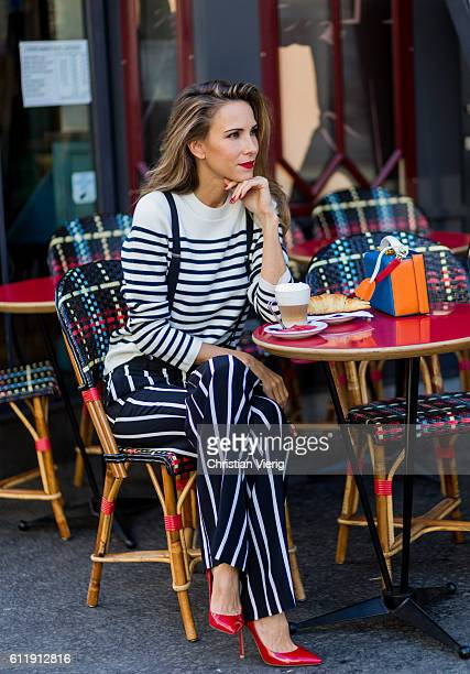German model and fashion blogger Alexandra Lapp sitting in a French Cafe drinking coffee and eating Croissant wearing striped jumper from Steffen...