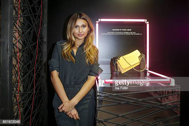 German moderator Wana Limar shows her own designed Liebeskind clutch at the Liebeskind Berlin housewarming party during the MercedesBenz Fashion Week...