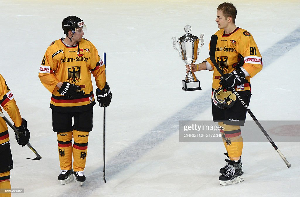 German Moritz Mueller (R) holds the winner trophy beside of his teammate Michael Wolf (L) after the winner ceremony of the German Cup ice hockey event in the Olympic hall in Munich, southern Germany, on November 11, 2012. Germany won the match against Slovakia 2-0 and won the tournament.